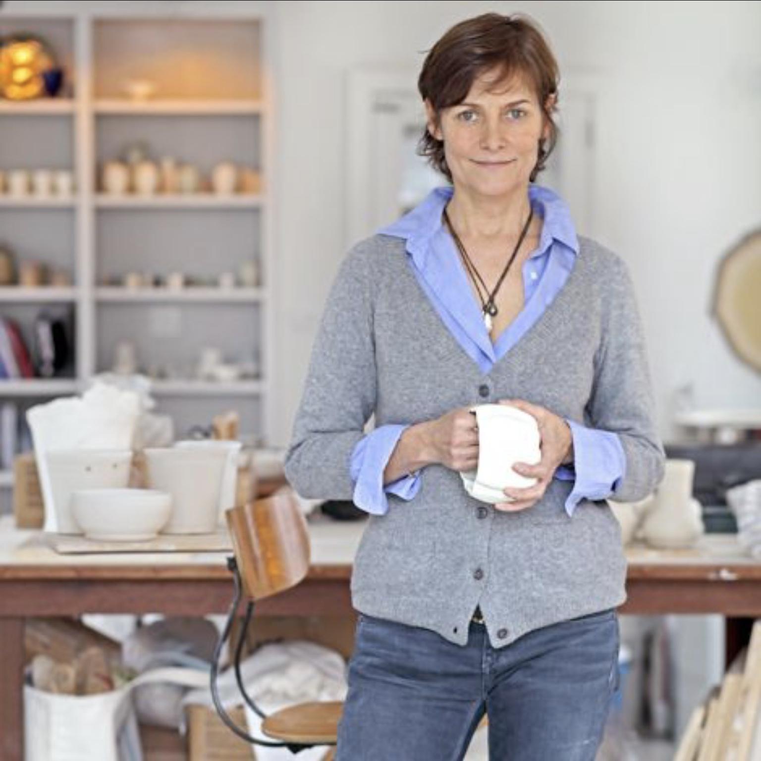 Photo of Carey standing in front of her ceramics