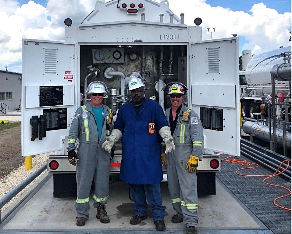 image of 3 LNG workers wearing grey and blue overalls and white hard hats standing in front of a LNG transfer truck