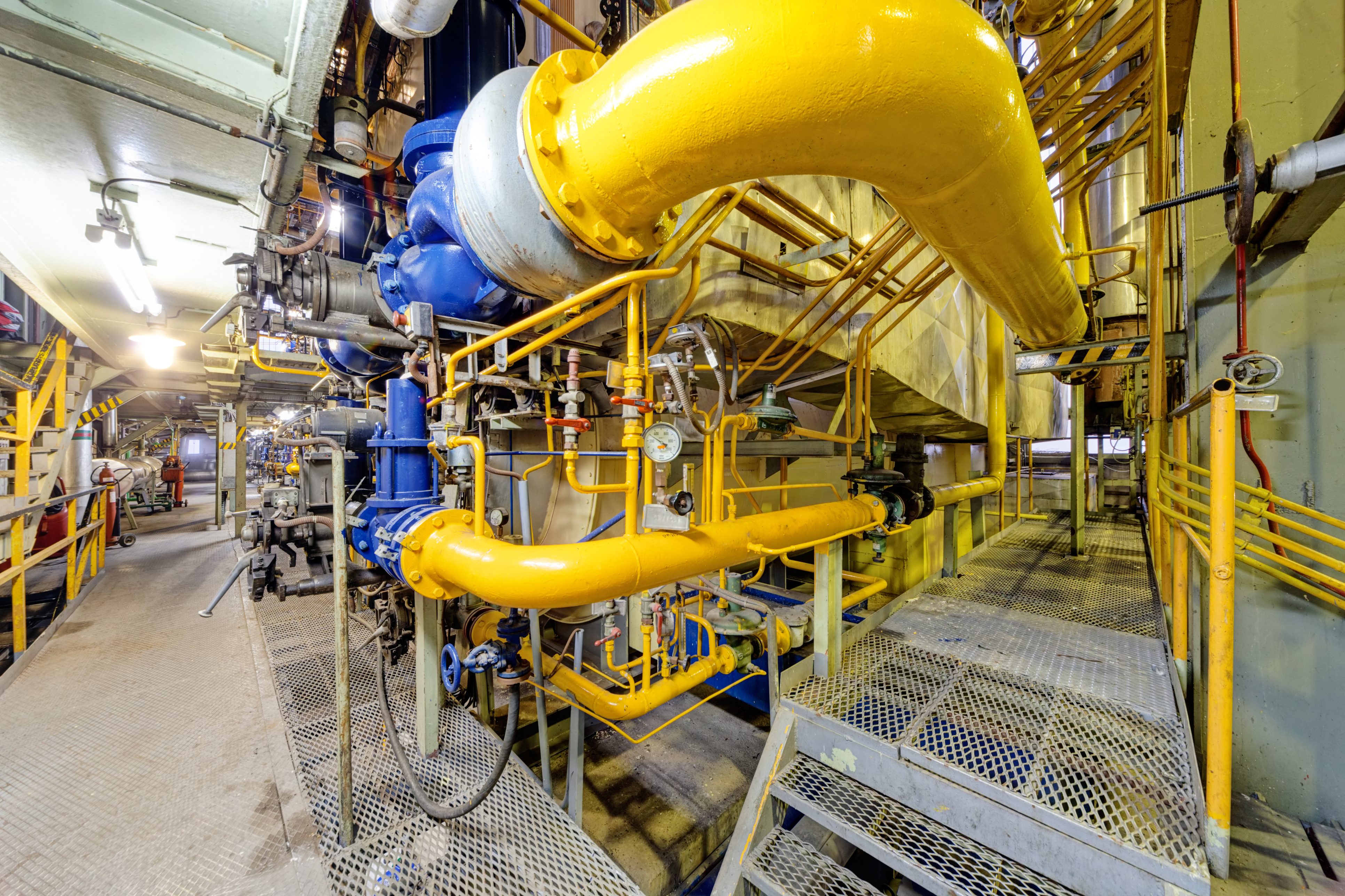 image of the interior piping of a natural gass plant showing bright yellow piping and scafolding
