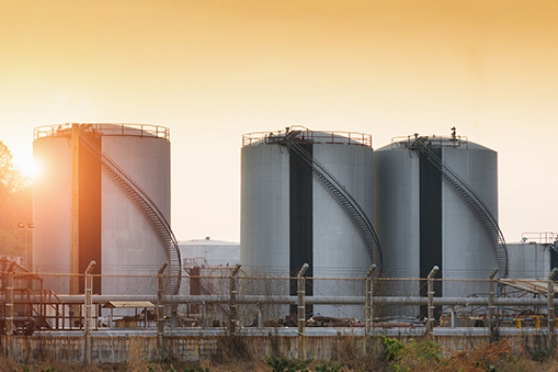 Image of three brushed steel LNG storage tanks against a backdrop of fields and a a sun filled sky of yellow and muted orange
