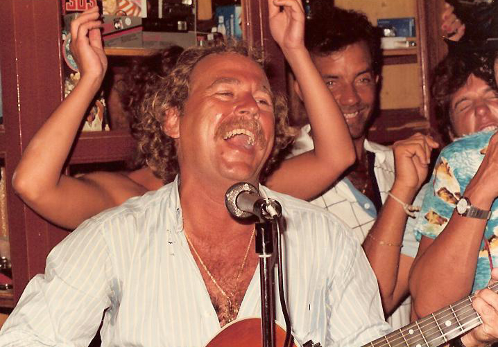Image of Jimmy Buffett playing guitar and smiling widely while playing to a close-knit group of young people.
