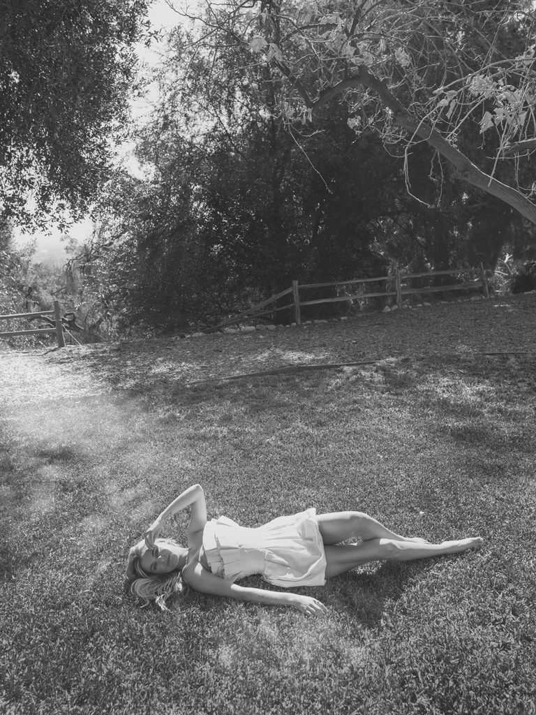 black and white photo Kelsea Ballerini laying down on the grass