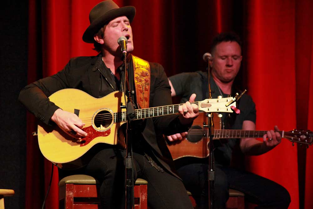 image of two men on stage sitting on bar stools, both playing acoustic guitars and singing under a spotlight