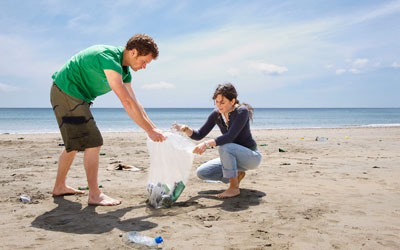 Two people cleaning up a beach