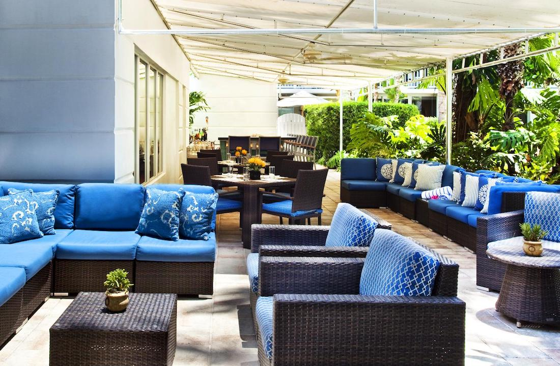 Outdoor patio with blue cushions on various sofas and chairs